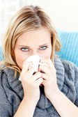 Sick woman using a tissue sitting on a sofa — Stock Photo
