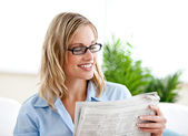 Attractive businesswoman wearing glasses and reading the newspap — Stock Photo