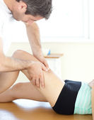 Handsome young physical therapist giving a leg massage — Stock Photo