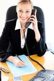 Self-assured businesswoman talking on phone and writing in her o — Stock Photo