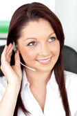 Serious young businesswoman with earpiece in a call center — Stock Photo