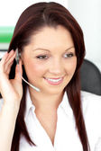 Positive young businesswoman sitting at her desk and wearing ear — Stock Photo