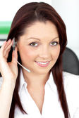 Attractive young businesswoman wearing earpiece in a customer se — Stock Photo