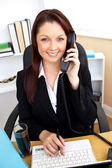 Self-assured businesswoman talking on phone and using her laptop — Stock Photo