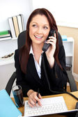 Assertive businesswoman talking on phone and using her laptop at — Stock Photo