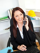 Ambitious businesswoman talking on phone using her computer — Stock Photo