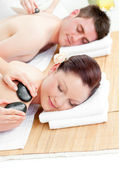 Lovely young couple receiving a back massage with hot stones — Stock Photo