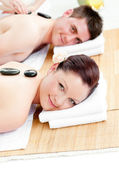 Cute young couple receiving a back massage with hot stones — Stock Photo