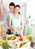Enamored young couple cutting vegetables in the kitchen — Stock Photo
