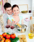 Close couple preparing spaghetti in the kitchen and drinkng wine — Stock Photo