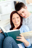 Happy couple reading a book in the living-room lying on the sofa — Stock Photo