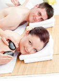 Attractive young couple receiving a back massage with hot stones — Stock Photo