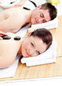Charming young couple receiving a back massage with hot stones — Stock Photo