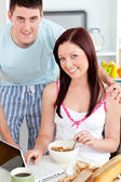 Smiling couple using a laptop while breakfast at home — Stok fotoğraf