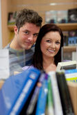 Caucasian couple looking for a book — Stock Photo