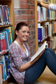 Smiling young woman reading a book sitting on the floor — Stock Photo