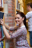 Charming young woman looking for a book — Stock Photo