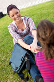 Two female students talking together sitting on the grass — Stock Photo