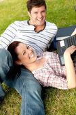 Par glada studenter använder en laptop liggande i gräset — Stockfoto