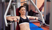 Beautiful athletic woman using a bench press — Stock Photo