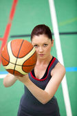 Portrait of a concentrated young woman playing basket-ball — Stock Photo