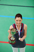 Smiling young woman holding a trophee and a medal — Stock Photo
