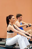 Athletic using a rower — Stok fotoğraf