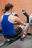 Athletic caucasian man using a rower — Stockfoto