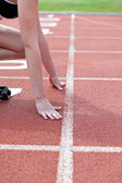 Close-up of a woman waiting in starting block — Stockfoto