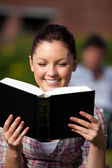 Smiling female student reading a book sitting on grass at — Stock Photo
