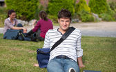 Good-looking male student lying on the grass with his schoolbag — Stock Photo