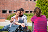 Happy couple of students sitting on grass talking with a female — Stock Photo