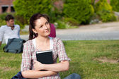 Thoughtful female student reading a book sitting on grass — Stock Photo
