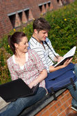 Young couple of students reading a book and using a laptop — Stock Photo