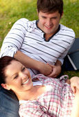 Positive couple of students sitting on grass and smiling at the — Stock Photo