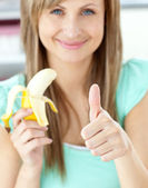 Smiling woman with thumb up holding a banana in the kitchen — Stock Photo