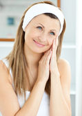 Young woman putting creme on her face wearing a headband in the — Stock Photo