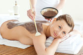 Delighted caucasian woman receiving a beauty treatment with mud — Stock Photo