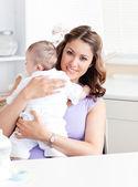 Positiva joven madre sosteniendo a su bebé en la cocina — Foto de Stock