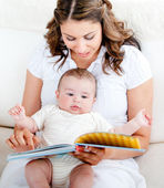 Loving mother reading a story to her adorable baby sitting on th — Stock Photo