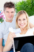 Enamored couple lying on the sofa with a laptop and a card — Stock Photo