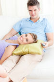 Affectionate couple watching television on the sofa in the livin — Stock Photo