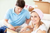 Ambitious young couple unpacking boxes with glasses — Stock Photo