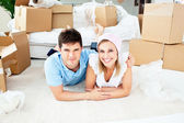 Jolly couple lying on the floor between boxes — Stock Photo