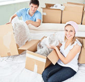Merry young couple unpacking boxes with glasses — Stock Photo