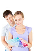 Enamored couple choosing color for a room — Stock Photo