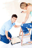 Beautiful caucasian couple painting a room — Stock Photo