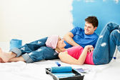 Happy couple relaxing after painting a room — Stock Photo