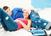 Happy νεαρό ζευγάρι χαλάρωση, αφού η ζωγραφική ενός δωματίου — Φωτογραφία Αρχείου