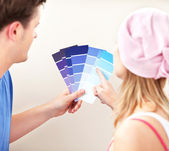 Concentrated couple choosing color for a room in their new house — Stock Photo
